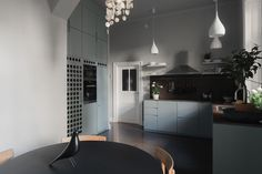 Scandianvian kitchen. pale blue cabinets, brown worktops and dark floors. White walls and lights with plants lighten it up