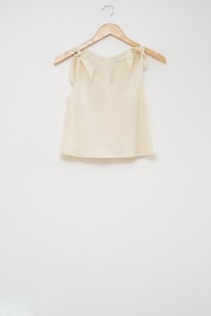 This crop top is made from the softest British woven wool crepe, with a silk lining. It is cut on the bias, with shoulder tie bows. It can be paired with the Oak Skirt as a two-piece ensemble outfit.  Pictured here in cream white.