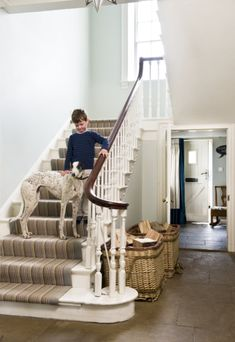 24 The staircase is 'wide enough for sledging down on trays' says Marion. Wall colour Farrow and Ball Pale Powder estate emulsion; large log baskets from Indigo; stair carpet Louis de Poortere 'Stripes', from Rodgers of York