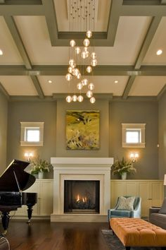 coffered ceiling, light fixture, trimmed picture box windows, built-in cabinets flanking flanking the fireplace, club chair, tufted ottoman = absolute perfection