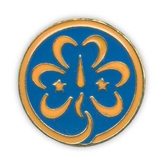 World Trefoil Pin - Three leaves representing the Girl Scout Promise, with a flame that represents the flame of friendship. The compass needle is to guide you, and the two stars are the Girl Scout Promise and Law. The outer circle represents the World Association, and the golden yellow trefoil on a bright blue background stands for the sun shining over the children of the world.
