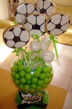 Para unos centros de mesa decora unos frascos con dulces en color verde y anéxale paletas en figuras de balón de fútbol. #FiestasTematicas #DecoracionFiestas
