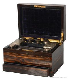 10 Pc. Vanity Set In Zebra Wood Box. 10 Glass containers with fancy engraved silver plated covers, unsigned. 3 perfumes, 2 decagon containers, 2 small round containers, 2 rectangular boxes and one long rectangular box (missing glass). In a zebra wood box with lift top over a singled drawer, brass hinged and purple velvet lined interior.  Presentation plaque on the top – Presented To Ellen Nichols,, Christmas 1880. Missing some minor veneer on the edges  Estimate: $400 – $600