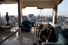 -, AL-SHAAS : Adel (R) and Mohammed (L) spend the afternoon in the only room of their home that was not totally destroyed in an apartment building that was hit by an Israeli missile during fighting between Israel and Hamas in the neighbourhood of Al-Shaas, in the north of the Gaza Strip, on August 16, 2014. AFP PHOTO/ROBERTO SCHMIDT