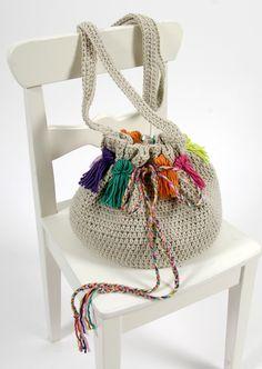 A réaliser au crochet avec les fils Natura Medium, ce sac à porter en bandoulière orné de pompons colorés et d'une cordelette multicolore saura trouver sa place dans vos accessoires