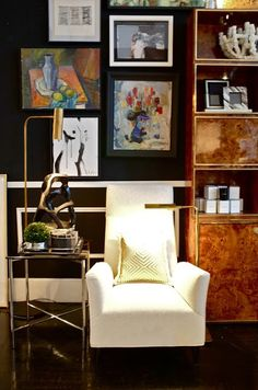 gallery wall, brass library/pharmacy lamp, burled wood cabinet, black wall