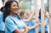 Cheerful teenage girl with volunteers building wooden frame in background