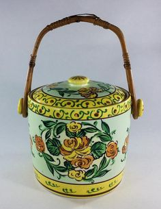 """Japan Biscuit Jar, Cookie Jar or Ice Bucket use any way you want.   Made in Japan in the 30's possibly.  Bamboo handle which has some damage.  Ceramic container and lid both have crazing. Lid has cracks and chips see pictures.  Container has a green tint to it yellow border and yellow and orange flowers.  5-3/4"""" tall or 8-3/4"""" with handle up. Bottom diameter is 5-1/8"""""""