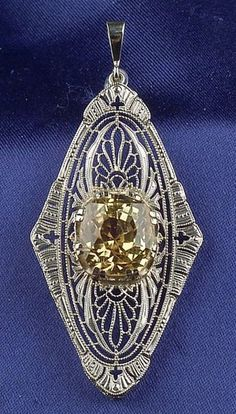 Art Deco Natural Yellow Sapphire Pendant, centering a cushion-cut sapphire measuring approx. 11.04 x 9.93 x 9.15 mm, 14kt white gold Art Deco mount.