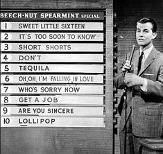 """Late 1950s: Dick Clark reviewing weekly """"top hits"""" during a segment of the American Bandstand TV show."""
