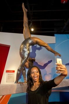 """Two-time Olympic gold medalist Gabby Douglas poses with the wax figure of herself at Madame Tussauds attraction in San Francisco, Calif., on Monday June 9, 2014.   """"I am stunned that there would be a Madame Tussauds wax figure even made of me at all, but to see the likeness and the incredible work they have done with it is even more overwhelming to experience today. I love that they created the figure with me actually doing a gymnastics routine on the balance beam!"""""""
