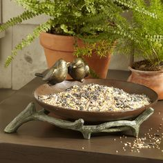 Lovebirds Bird Feeder   Rustic and charming, this feeder features an aluminum tree branch cradling a wooden bowl with two courting birds snuggling on the edge. Sits gracefully on a terrace rail or end table.
