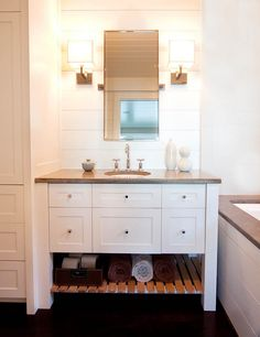 Beach cottage bathroom - white decor, soaking tub, stone counter and tub tops, doubled edge mirror, lots of storage, square sconces, dark wood floors