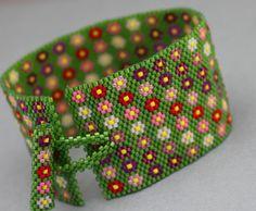 Il braccialetto bracciale fiore ha uno sfondo verde medio con varie tonalità di fiori rosa e rossi. Misura 1,5 cm di larghezza. Le dimensioni del polso sono tra 6,75 e 7 pollici, ma possono essere regolata su richiesta.    Il bracciale è stato realizzato utilizzando perline delica con punto peyote.    Se avete domande, si prega di contattare me.    Grazie per il tempo! Per visualizzare altri miei oggetti in vendita, prego vist il mio negozio a http://www.etsy.com/shop/Kath...