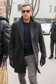 Stand out among other stylish civilians in a charcoal overcoat and grey jeans.  Shop this look for $109:  http://lookastic.com/men/looks/crew-neck-sweater-jeans-gloves-sunglasses-overcoat/6498  — Black Crew-neck Sweater  — Grey Jeans  — Black Leather Gloves  — Black Sunglasses  — Charcoal Overcoat