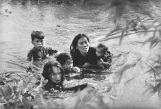 1965 - A mother and her children wade across a river to escape US bombing. The US Air Force had evacuated their village because it was suspected of being used as a base camp by the Vietcong. (Kyoichi Sawada)