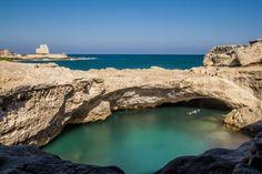 """La Grotta della Poesia (dal greco """"sorgente di acqua dolce"""") a Roca e sullo sfondo la torre di Roca Vecchia"""