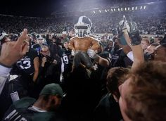 Michigan State players put a spartan helmet on the Paul Bunyan trophy after MSU's 29-6 win over Michigan in East Lansing on Saturday, Novemb...