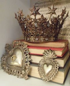Metal hearts and a crown fit for a princess perched on some vintage books. Shelf candy!