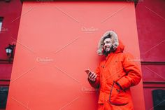 handsome young male student with toothy smile and beard stands on red wall background, facade of educational institution in red winter jacket with hood with fur, Uses finger on screen of mobile phone , Restaurant Website Templates, Red Walls, British Indian, Ivory Coast, Republic Of The Congo, Facade, Hooded Jacket, Finger, Handsome