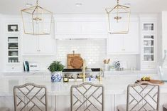Designed to perfection, this beautifully appointed white kitchen features two Regina Andrew Design Camden Five-Light Lanterns hung above a white kitchen island donning a carrera marble straight edge countertop seating gray bamboo counter stools and holding a sink paired with a brass gooseneck faucet.