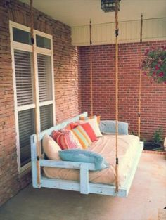 Recycled Pallet wood swing with colorful pillows. Great idea for the front porch.
