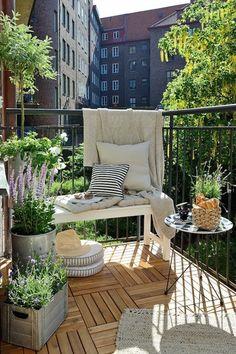 balcon fleuri, sol en bois, petit banc blanc, tapis beige à franges, table ronde en blanc et noir