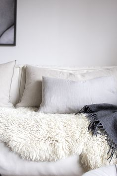 Cozy textures, lush layers and elegant neutrals. This sheepskin styling idea is simple and cozy: drape it over your bed or couch for a cushy place to sit with an extra dose of style! A charcoal gray cashmere throw ups the cozy factor even more.