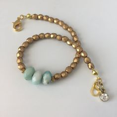 Fancy Boho Bracelet made with 3 Amazonite gemstones, glass Picasso beads and gold metal beads, has a simple rhinestone embellishment and is completed with a gold lobster claw clasp. At 8 long, this elegant Boho bracelet is made for most standard size wrists and is lightweight and simple. This is the perfect gift for lovers of bohemian style, gemstone, nature, and Hygge.