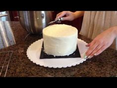 Frost a Cake With a Viva Paper Towel for A Smooth, Professional Look.  Go to 7mins 15 secs to watch this part only.  Basically, place Viva paper towel on icing and with long delicate strokes with the length of your hand,  apply very gentle passes to smooth out the frosting.  Kinda like petting a dog or cat's back from head to tail. If your frosting is soft, refrigerate for a while so it's easier to smooth out.