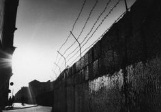 Sunlight shines on the barbed wire and blocks of the Berlin Wall in August 1961