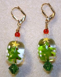 Handcrafted by Teal Palmetto, LLC. These earrings sparkle and shine just like the star at the top of the Christmas tree!  The clear glass focal beads have two Christmas trees handpainted on each of them in green, white, yellow, and red.  Each earring has a red glass accent bead, a green accent bead, and a sparkling white Swarovski crystal bead.  This pair has gold leverback ear wires.  Price: $15.