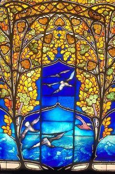 jugendstil stained glass. Compositie:  Symmetrische opbouw. In het midden is er een bewegende voorstelling te zien.  Vorm: Organische vormen Kleur: kwaliteitscontrast, warme kleuren in de bladeren, en koude in de lucht dus ook een warm koud contrast.