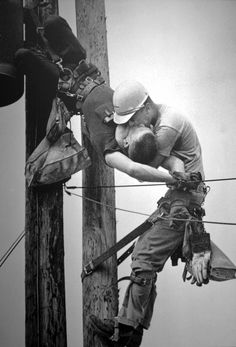 """The Kiss Of Life by Rocco Morabito, 1968 Pulitzer Prize. Jacksonville Journal photographer Rocco Morabito is on his way to photograph a railroad strike when he notices Jacksonville Electric Authority linemen high up on the poles. """"I passed these men working and went on to my assignment,"""" says Morabito. """"I took eight pictures at the strike. I thought I'd go back and see if I could rind another picture."""""""