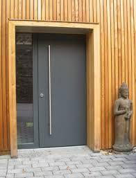 שילוב מקורי אך לא מוגזם של סרגלי אלומיניום לאורך(חריג) עם דלת אלומיניום בצבע אפור בתנור + משקוף חובק פורניר. ליצירת מראה שאין בשום מקום, המשלב בין קרירות של המתכת והחמימות של העץ. moderne Haustür