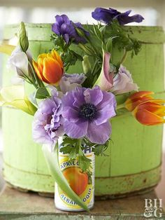 Get creative with alternatives for vases. Here, we used a charming fruit-juice can. Cup off the top and fill with something heavy, such as small marbles or pebbles. Fill with water and place flowers, such as anemones, tulips, calla lilies, and lisianthus as pictured.