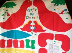 A big printed heavy cotton fabric panel for making Dexter the Dinosaur. a bright red cartoon dinosaur with yellow-orange spikes and green bow tie.