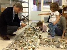 Reggio Emilia mayor enjoys an interactive exhibit of natural materials with young explorers.