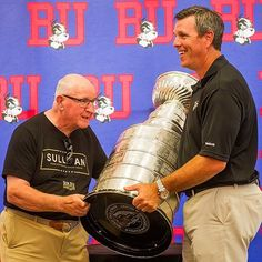 ICYMI the #StanleyCup made its way to BU this week! Pittsburgh Penguins head coach (and @TerrierHockey alum) Mike Sullivan (Questrom90) brought the 2016 Cup to Agganis Arena to celebrate with supporters of the BU mens hockey program. The former Terrier hockey stars father Walter Sullivan helps him hoist the massive trophy won by the Penguins this year! #ProudToBU