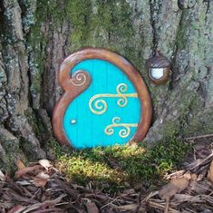 A lovely curlyque fairy door for your garden, which comes with an acorn porch light - what fairy could resist! A Jul McFillin original, this unique door is aqua with gold hinges and a woodtone frame. It also comes with an acorn porch light with glass! It looks adorable against a tree, a porch step or even indoors against a wall.  It measures 4.25 tall and 4 wide, and is made with fairy dust, resin, acrylic paint and a weather resistant topcoat. I designed the mold myself, and it is…