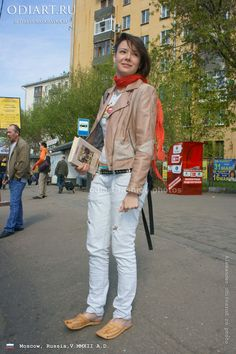 Street fashion in Moscow, Russia. May 2012. Random photo. Short women's leather jacket. Jeans with holes. Belt with rivets. odigif@gmail.com photo.