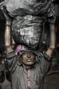 """Bearer of coal in Kolkata (formerly Calcutta), the capital of the Indian state of West Bengal.  Visit http://robertopazziphotography.weebly.com, subcribe to the newsletter and download the ebook """"Streets of the World"""" as welcome gift!  Web Site: http://robertopazziphotography.weebly.com/ Facebook: Roberto Pazzi Photography Instagram: Roberto_Pazzi_Photography"""