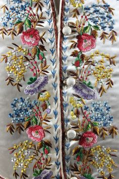Detail of an embroidered gentleman's waistcoat early 19th century, of ivory satin worked in floss and corded silks with wildflowers.