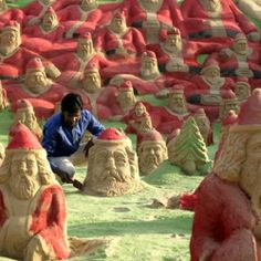 500 Santa Clauses Sculpted into the Sand in India...some Buddha looking Santas