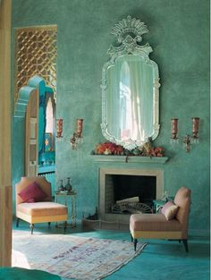 Gorgeous Moroccan styled sitting area by the fireplace. Green walls, amazing detailed mirror, high ceilings and ornate golden arches by Amer...