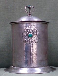 An Art Nouveau Guild of Handicraft cylindrical silver biscuit barrel and cover complete with green glass liner. The exterior decorated with three tree designs set with a single green cabuchon, the cover with stylized green finial. Designed by Charles Robert Ashbee. 14.5cm diameter at base. 18cm high. Estimate £10,000-15,000. To be sold in our October Fine Art auction.