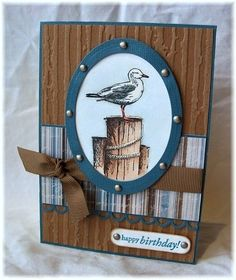 handmade card ... beach theme ...  ikonic seagull on a pole photo ... like the metal brads on the framing ... hints at a ship's porthole ... love the rich browns and blues in the background ... embossing folder texture ... great card!!
