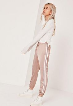 we're going all out when it comes to athleisure. rock the workout look to the streets and beyond in these satin joggers. in a neutral nude shade with contrast white stripe panel, sweet satin feel with high shine, cuffed ankles and an elasti...