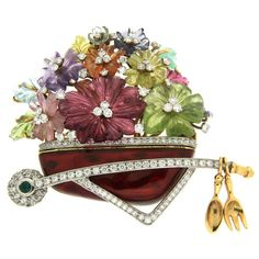 Carved Flower Gemstone Gold Platinum Wheelbarrow Brooch The wheelbarrow brooch is made in 18kt yellow gold and platinum, it features special cut gemstones such as citrine, peridot, tourmaline and amethyst. A green beryl is set in the center of the wheel, and 4.47 carat total weight of round brilliant diamonds are encrusted on the red enamel section. https://www.1stdibs.com/jewelry/brooches/brooches/