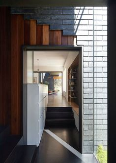 In some parts of the interior of this modern house, there are glimpses of the exterior materials (grey slate tiles and wood) flowing through to the interior.